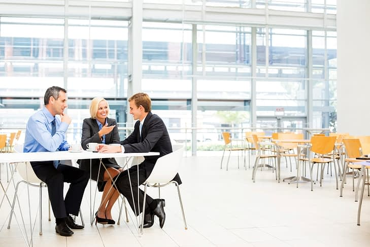 Full length of businesspeople in discussion during coffee break in cafeteria. Horizontal shot.