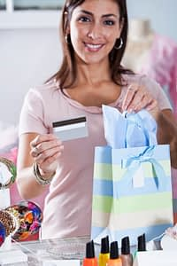 Woman in boutique with creditcard and shopping bag